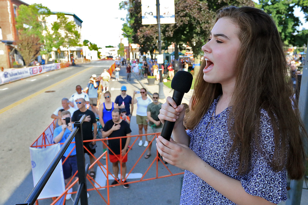 . Singing the national anthem is Mary Mahoney, 15, of Fitchburg to start the Women\'s Pro C 1/2 during the Longsjo Classic in Leominster on Saturday. SENTINEL & ENTERPRISE/JOHN LOVE