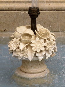 the base and nozzel of a fountain along the fountain garden wall