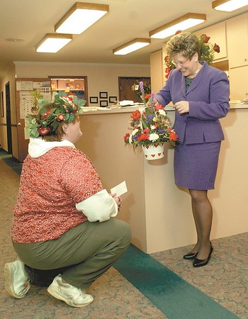 Cupid, Patty Winn, delivers a singing valentine to Jo McMorris from some of her clients in 2003. Winn had a busy day delivering the singing valentines to lucky recipients for K & M Floral Shoppe.<br /> 	Eric Williams photo