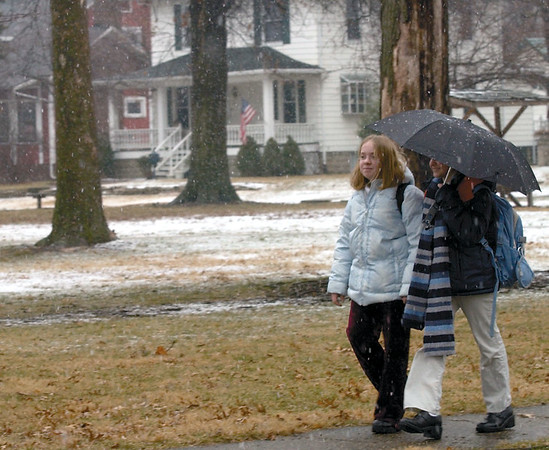 Kelsey Fox, 11, left, and Cindy McMillan, 10, try to keep a little snow of of themselves under an umbrella as they walk home from school in 2003.<br /> Eric Williams photo
