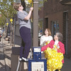 Angie Jones, on ladder, hangs a yellow ribbon on one of the light poles along Jefferson Avenue in Effingham as Ann Will, center, and Linda Riley hold more ribbons to be hung in this 2003 photo. Employees of Fifth Third Bank hung ribbons made by The Last Straw in downtown Effingham for the military personnel.<br /> Eric Williams photo