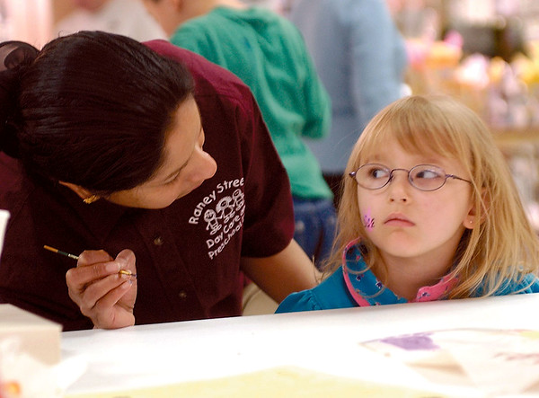 Nicole Crozier, 5, sits patiently as Fouzia Osman stops to check her progress as Crozier gets a kitten painted on her cheek at the Kid Fair at the Village Square Mall in in this 2003 photo.<br /> Eric Williams photo