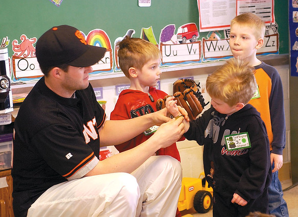 Ryan Cox, left, shows some of the students at Altamont Head Start 2 some of his equipment during a stop to read to the kids in this 2003 photo. Cox, who is a pitcher with Shreveport Swamp Dragons, stopped to read to the kids and tell them about being a major league pitcher.<br /> Eric Williams photo
