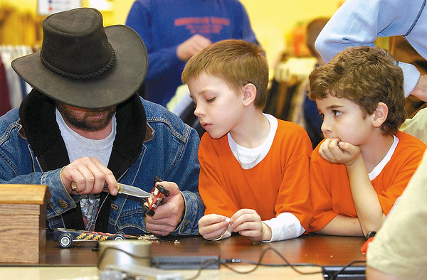 In this 2003 photo, Cody Wood, 7, center, and Tanner Austin, 7, look on as Cody's dad Brent Wood works on taking a little weight off their cars at the check in at the Boy Scouts Pinewood Derby at the Village Square Mall in Effingham.<br /> Eric Williams photo