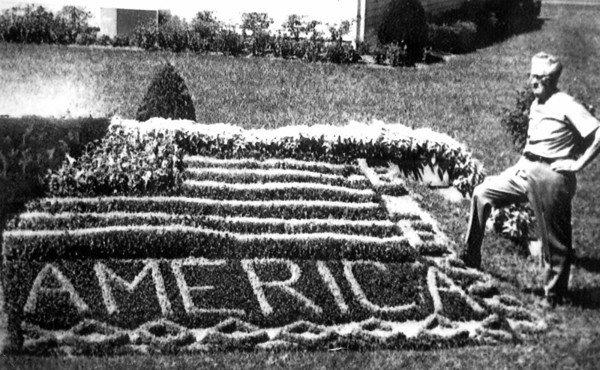 """in this 1970 photo taken in Altamont, Edward Torbeck, 70, stands beside a floral design of an American flag along with the message """"God Bless America"""" he created with 2,019 plants. The retired St. Louis barber said at the time he had happy flowers because he gives them a drink of a beer solution twice a  month."""