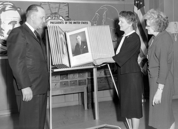 Mayor looking over portraits of presidents in 1963