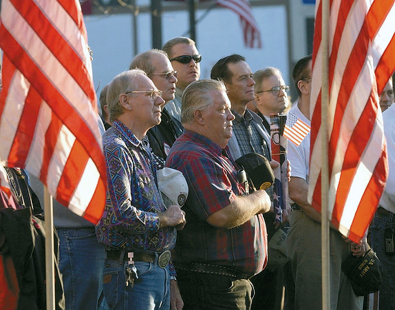 "Veterans cover their hearts as the Rev. Jason Rensner sings ""God Bless America"" at a rally in support of US troops at the Effingham Courthouse lawn in this 2003 photo.<br /> Eric Williams photo"