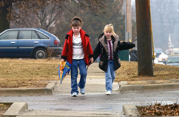 Amanda  Guthrie, 6, left, is prepared for a wet morning as she and Megan Levitt, 6, wait for the school bus in Effingham in this 2003 photo. <br /> Eric Williams photo