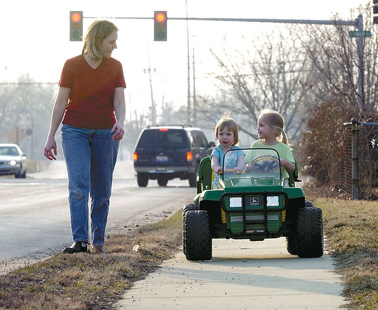 Kaitlyn Zeller, 2, center, looks a little nervous as her sister Grace, 3, watches their mom Nicole instead of the road as they take a drive in Effingham in this 2003 photo.<br /> Eric Williams photo