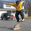 Jake Janis ollies over a stack of wood blocks as Brendan Keller looks on as they take advantage of the warm weather to work on their skateboard moves in Effingham in this 2003 photo.<br /> Eric Williams photo