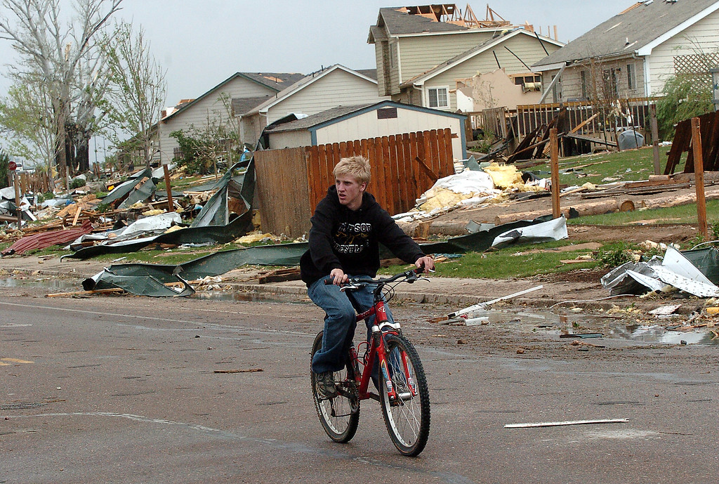 . A resident rides his bike past houses damaged by the 2008 tornado on Garden Drive in Windsor. (File Photo by Steve Stoner/Loveland Reporter-Herald)
