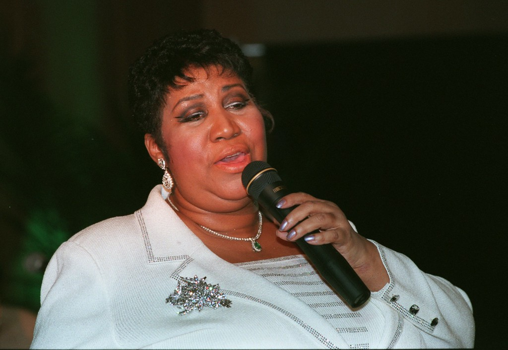 ". Motown legend Aretha Franklin sings Silent Night during a concert for patients at Henry Ford Hospital in Detroit yesterday afternoon. The half-hour show, that had the feel of a church revival, consisted mostly of gospel numbers. Looking around at the room full of people, many of whow were in wheelchairs , with Ivs in town, Franklin said, ""For the next twenty minutes or so, No body in here is going to be sick.\"""