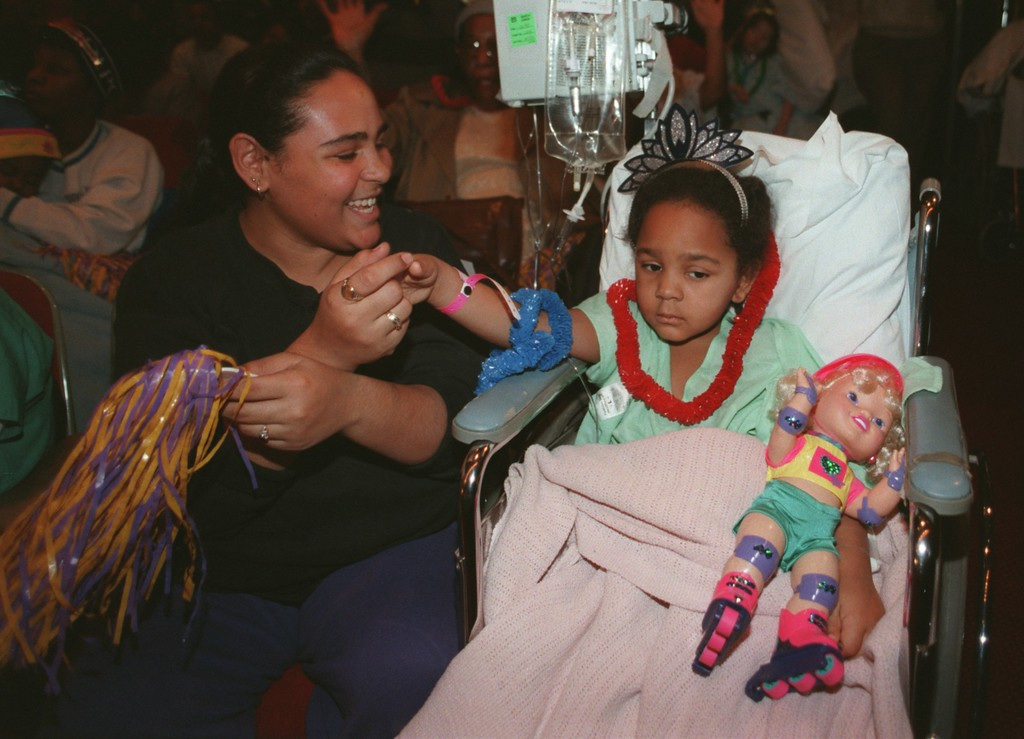 . Pediatric patient Jessica Gonzalez,6, of Southwest Detroit, gets a hand cheering from her mom Jacqueline at the Aretha Franklin concert yesterday afternoon at Henry Ford Hospital in Detroit.