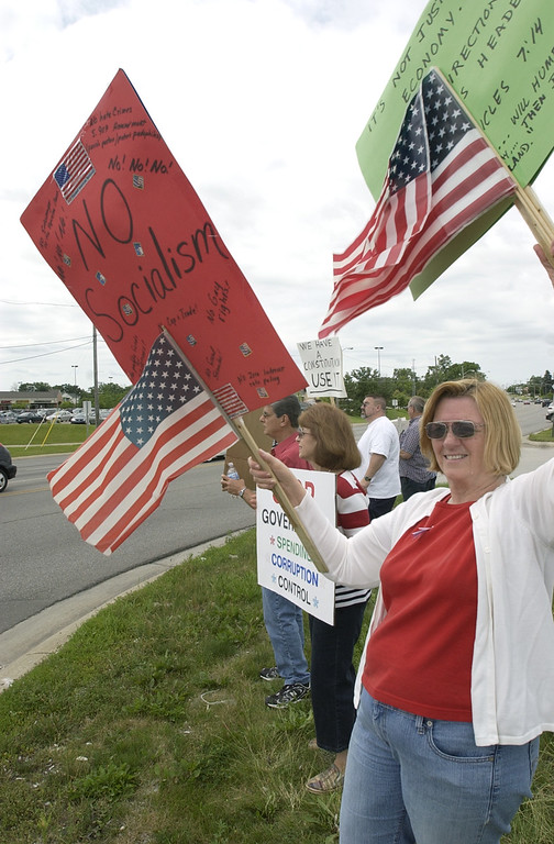 . (From front to back): Jan Recktenwald, Grace Madaffer, and her husband, Tony Madaffer, stand at the corner of Crescent Lake Road and M-59 on Saturday to take part in a tea party. Grace said they came out because they want to be heard, but feel their representatives in government aren\'t listening. Photo taken on Saturday, July 4, 2009, in Waterford, Mich.  (The Oakland Press/Jose Juarez)