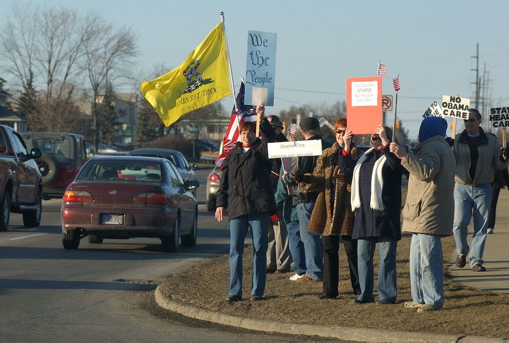 . A group of Tea Party activists rally along Rochester Road, south of Hamlin Road, as they protest near a location where he was scheduled to speak.  Photo taken on Friday, March 5, 2010, in Rochester Hills, Mich.  (The Oakland Press/Jose Juarez)
