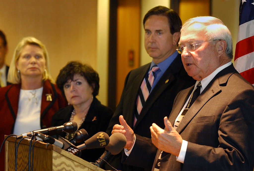 """. (from left) Ruth Johnson, Oakland County Clerk/Register of Deeds, Jessica Cooper, Oakland County Prosecutor, and Michael Bouchard, Oakland County Sheriff, listen as L. Brooks Patterson, Oakland County Executive, talks about their efforts to investigate fraudulent \""""Tea Party\"""" election filings during a press conference in the lobby of the Executive Office. (Oakland Press Photo: Vaughn Gurganian)"""