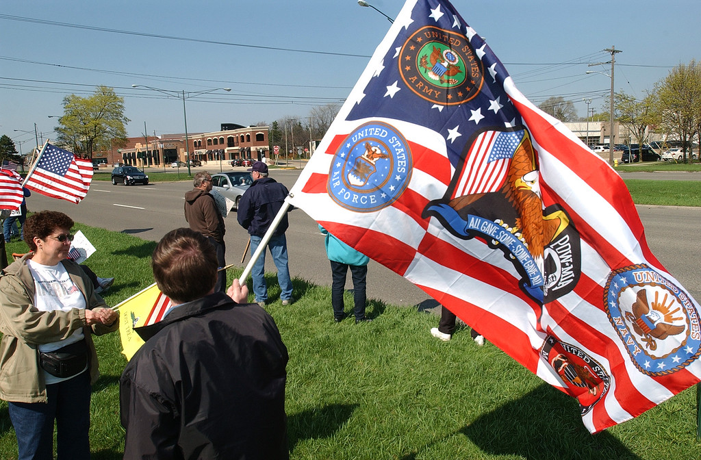 . Jim Helegda of Royal Oak, Mich., waves a patriotic flag along Woodward Avenue during a Tea Party rally.  Photo taken on Saturday, April 10, 2010, in Birmingham, Mich.  (The Oakland Press/Jose Juarez)