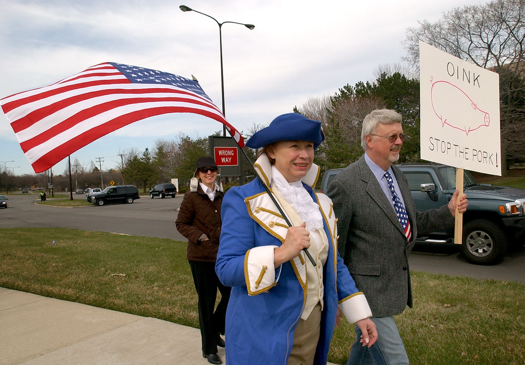 """. Diane Schrift, left, of Birmingham, Mich., who is dressed as a \""""Revolutionary Patriot\"""" walks with her husband, Tom Schrift, as they head for the Tax Day Tea Party.  Photo taken on Wednesday, April 14, 2009, in Troy, Mich.  (The Oakland Press/Jose Juarez)"""