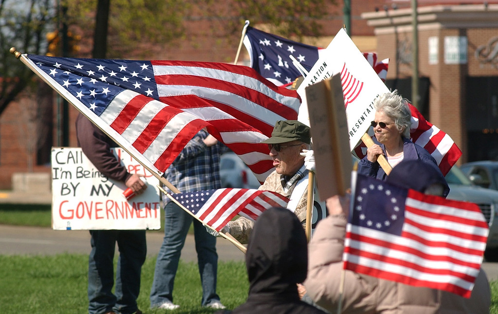 . Attendees of a Tea Party rally brace themselves against the high winds as they listen to a speech.  Photo taken on Saturday, April 10, 2010, in Birmingham, Mich.  (The Oakland Press/Jose Juarez)