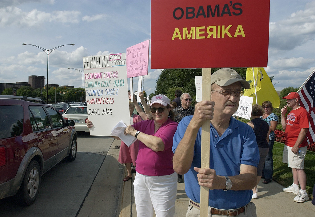 . Marvin McBroom, foreground, shows his displeasure with the Obama administration as he and several hundred other protestors gathered for a Tea Party, at the corner of Big Beaver and Coolidge Roads in Troy, Mich., Thursday, July 30, 2009.  (The Oakland Press/Jose Juarez)