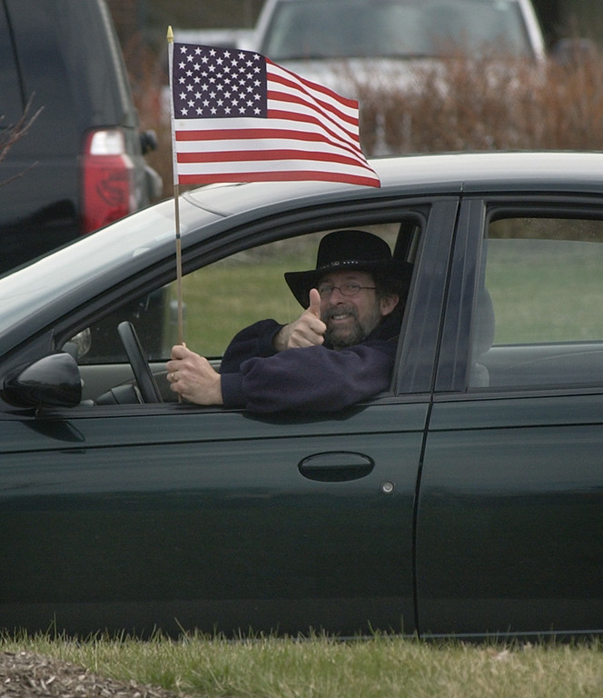 . An unidentified motorist, with the American flag in hand, acknowledges the crowd as he sits in congested traffic, along Big Beaver Road during the Tax Day Tea Party.  Photo taken on Wednesday, April 14, 2009, in Troy, Mich.  (The Oakland Press/Jose Juarez)