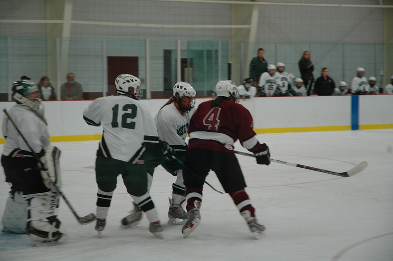 Two defensemen and the goalie focused on Abby Ostrom in front of the net.