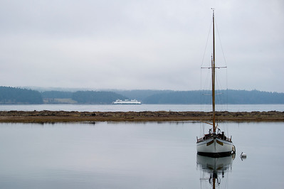 A ferry in San Juan Channel passes a moored sailboat in Fisherman Bay.