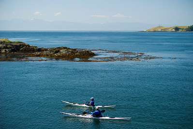 Two kayakers approach Deadman Island at Shark Reef. Cattle Point Lighthouse on San Juan Island is in the background.