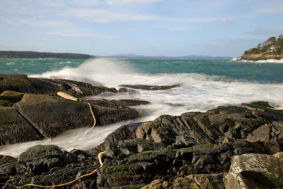 February 25, wind-tossed spray hits the pillow rocks near King Point and Shark Reef.