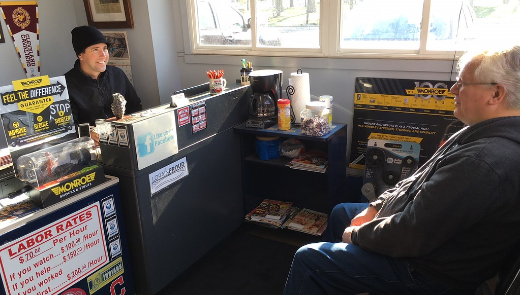 . Richard Payerchin - The Morning Journal <br> Left, Muzik\'s Auto Care owner John Muzik talks to customer Paul Bartulica in the shop office at 704 W. Erie Ave., Lorain, on Nov. 9, 2017. The garage, which also uses the name Muzik Bros., this year is celebrating its 75th anniversary in business.