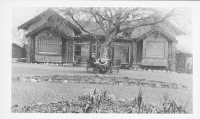"Percy T. Morgan and his wife, Fanny Ainsworth Morgan, sit in front of the home known as ""Little Gables"" owned by Percy's father, ""Cosmo"" Morgan. The house was built circa 1909."