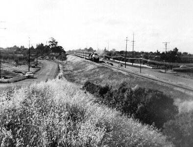 The evening Southern Pacific passenger train from San Francisco passes through Los Altos between El Monte Avenue and Springer Road in the mid-1950s.