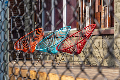 Orange, blue, red colored metal/plastic chairs on a verandah LA California.