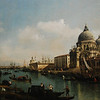 View of the Grand Canal and the Dogana<br /> <br /> Bernardo Bellotto <br /> Italian, Venice, about 1740 <br /> Oil on canvas <br /> 53 1/4 x 91 1/4 in. <br /> <br /> Bernardo Bellotto was the nephew of Canaletto, a painter renowned for his idealized views of Venice. Together they produced many painted vistas for tourists who stopped in Venice on their Grand Tour of Italy. Grand Tourists would have purchased these types of paintings as souvenirs and reflections of their cultural sophistication. <br /> <br /> In this architectural record of Venice and the Grand Canal, Bellotto presented a cross-section of Venetian society going about business on a sunny morning. Light from the east falls upon the Palazzo Pisani-Gritti with its arched windows and painted façade. A Venetian devotional box housing various types of religious icons hangs below the arched windows of the building at the left. Such boxes were usually placed on a building right next to the canal so that passers-by could pause for a moment of prayer upon leaving or arriving. <br /> <br /> Its image reflected in the canal, the Baroque church of Santa Maria della Salute dominates the right bank. Next to it, behind a shadowy row of houses, stands the Gothic façade of the Abbey of San Gregorio. On the far right is the Dogana or customs building. Gondolas and ferries, modes of transportation still in use today, traverse the water between the two banks. The mouth of the canal, where seafaring vessels leave or enter the city, is visible in the distance.