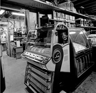 Warren Rowe's Jukebox repair shop in El Monte. The last of a kind  master who once worked for Seeburg in Chicago and knows every schematic, wire color, tube, capacitor, fastener and chrome plated part from memory. A 1955 Seeburg V200 is in the foreground, from June 25, 2003.