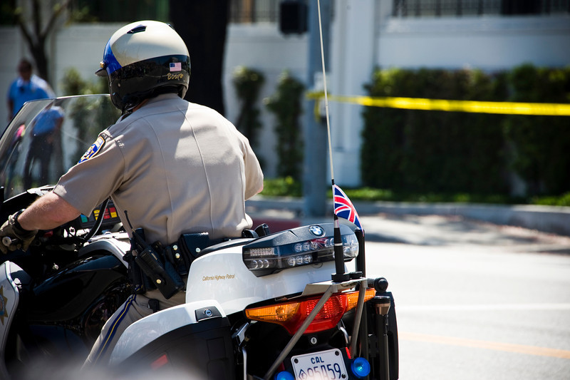 A police officer securing the area where the royal couple are expected to exit. A British flag adorns the motorcycle.
