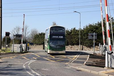 1004 crosses the railway at Kirknewton 21st April 2021