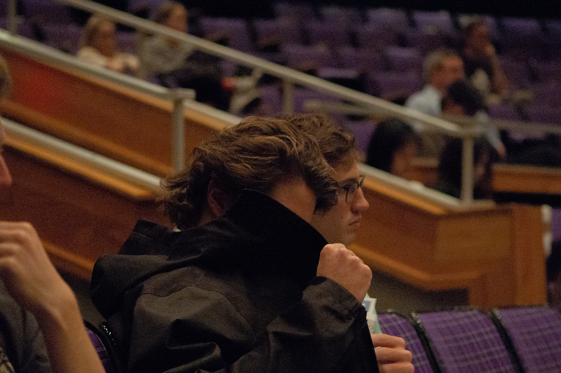 Ducking behind the collar of their jacket a Kansas State Student puts some papers in a pockets during Carolyn De Witt lecture over the impact of youth voting. De Witt, Executive Director of Rock the Vote, came to Forum Hall at the Student Union to inform Kansas State students about the importance of their vote. One key element of her lecture is that many states make it hard for college students to access their vote. (Rowan Jones|Collegian Media Group)