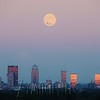 """Photographer Jacob Zimmer captures the full """"Supermoon"""" rising over the Downtown Louisville, KY skyline from across the Ohio River in Southern Indiana while the setting sun reflects off the glass windows of the city skyscrapers. An airline jet can be seen crossing in front of the moon descending to the Louisville International Airport. Monday, September 8, 2014."""