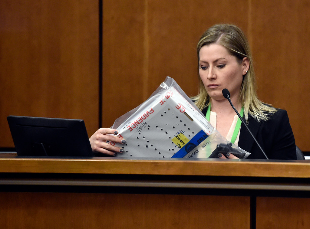 . BOULDER, CO - FEBRUARY 13, 2019:  Boulder Police Department Detective Kara Wills looks at a handgun submitted as evidence during the Louis Sebastian trial on a charge of first-degree murder in the May 2017 shooting of Christopher King, 49, at the Boulder County Justice Center on Wednesday at the Boulder County Justice Center in Boulder. For more photos of day 2 of the trial go to dailycamera.com  (Photo by Jeremy Papasso/Staff Photographer)