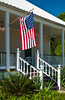 A plantation cottage verandah with an American flag and stairs on the Great River Road, Louisiana, USA, America.
