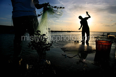 MISTY LEIGH MCELROY/FOR THE COURIER Ricky Nelton (R), of Montegut, reels in his cast net as Michael Blanchard, of Chauvin, throws his castnet into Robinson Canal from the pier at Lapeyrouse Seafood in Chauvin Tuesday afternoon.