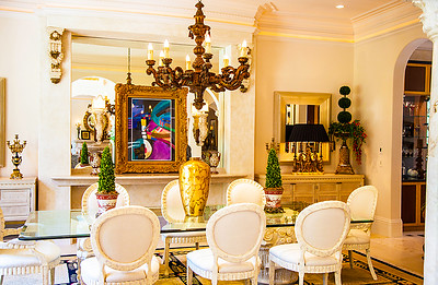 The Dining Room — The dining room has a gorgeous built in marble buffet, perfect for entertaining. The expansive glass dining room table for twelve has Corinthian Caps as its base, each weighing over 2,000 lbs.