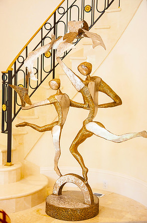 "The Grand Foyer — The Grand Foyer also showcases gorgeous works of art. Within the alcove of the flawless circular staircase, a hammered bronze statue called, ""The Dancers"", by artist Colbert Collins — adds a whimsical elegance."
