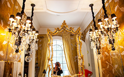 The Powder Room — The gold leafed mirror upon a mirror and premier quality crystal candelabra wall sconces make the room glimmer magically. The countertop is one solid piece of marble.