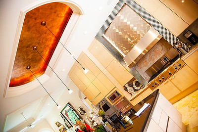The Kitchen — The huge granite island in the center of kitchen is domed by a graceful bronze leaf shimmering down from overhead.