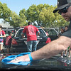 Tommy Arzate, foreground, cleans the hood of a police cruiser while more volunteers detail another car in the background during a service day in Fullerton on Saturday, April 29, 2017. (Photo by Matt Masin, Orange County Register, SCNG)