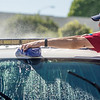 Jason Johnson of Fullerton stretches across the hood of a police cruiser to cover it in soap while volunteering on a Fullerton service day in Fullerton on Saturday, April 29, 2017. (Photo by Matt Masin, Orange County Register, SCNG)