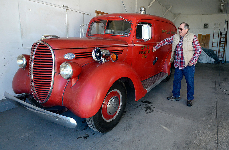 Fran Lyons, a longtime former Loveland firefighter, opens the door of a 1939 Ford Tuesday, Dec. 5, 2017, that was used as an ambulane at one time and then was used as a rescue vehicle. In addition to their collection of antique trucks, the Loveland Fire Exhibit recently purchased a 1952 hand-built ladder firetruck that used to be in service in Loveland.  (Photo by Jenny Sparks/Loveland Reporter-Herald)