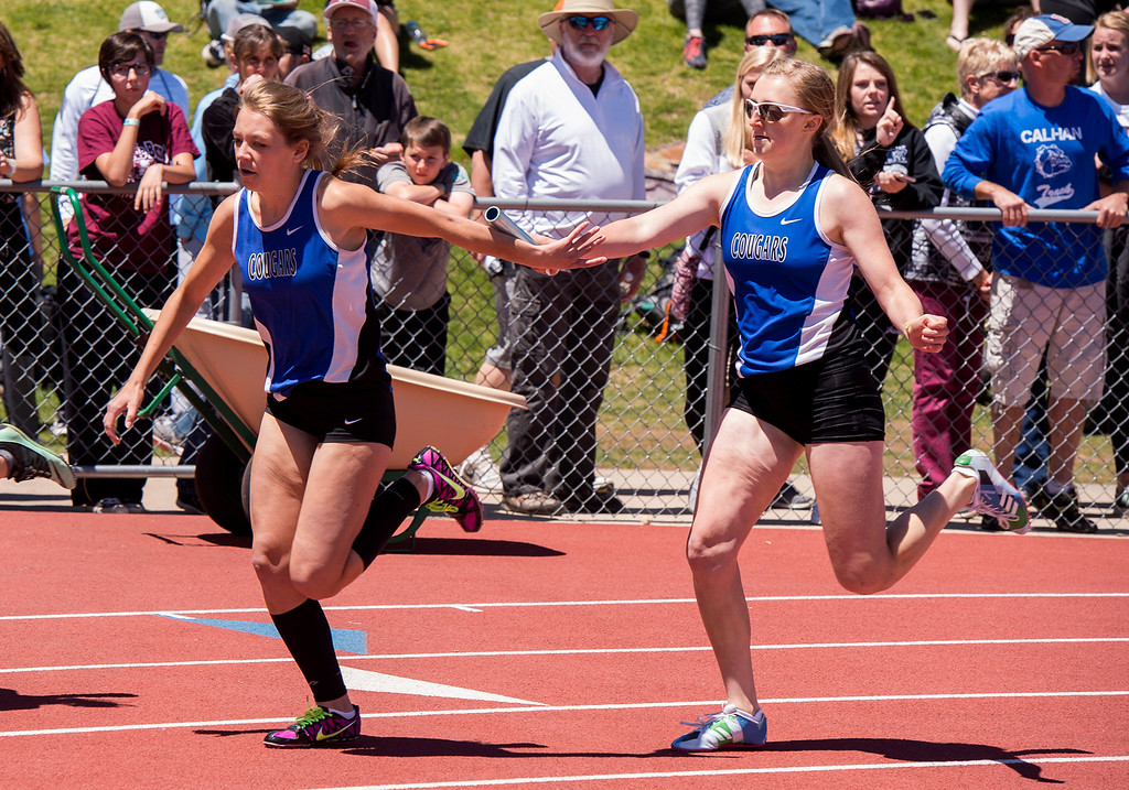 . Resurrection Christian\'s Alexa Brolsma, left, and Molly Watson, right, pass the baton during the 2A Girls 4x200 relay Saturday afternoon May 20, 2017 at Jeffco Stadium in Lakewood. (Michael Brian/For the Reporter-Herald)